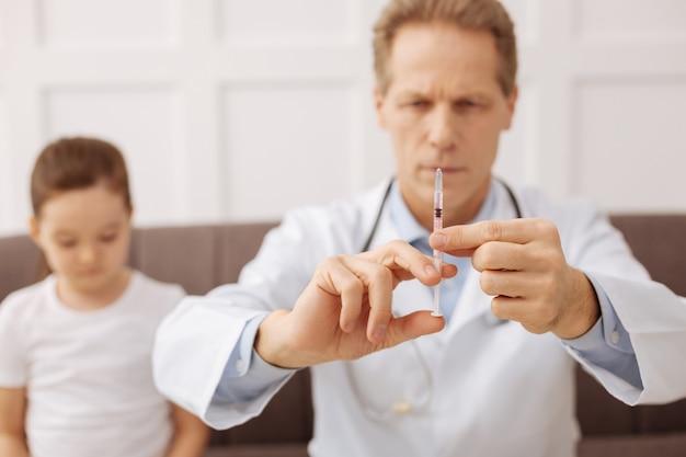 Nauwkeurige dosering. vastberaden, goed opgeleide, bekwame kinderarts die zijn patiënt een vaccinatie wil geven nadat ze klaagde over pijn in haar keel