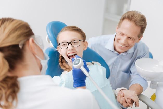 Nauwkeurige geweldige slimme tandarts die een procedure uitvoert met professionele apparatuur terwijl de ouder naast zijn meisjes zit en haar ondersteunt
