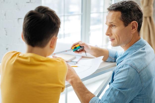 Nauwkeurige maat. aangename jonge vader die meetlint laat zien aan zijn zoon, die aangeeft hoeveel centimeters nodig zijn om samen iets te bouwen