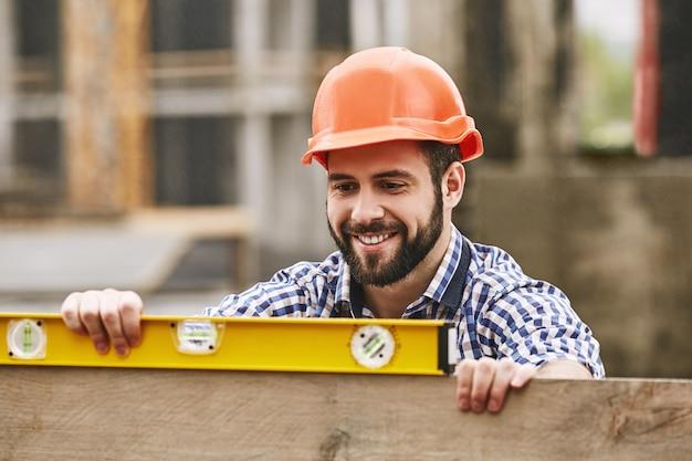 Nauwkeurige metingen vrolijke bouwvakker in beschermende gele helm die het niveau controleert