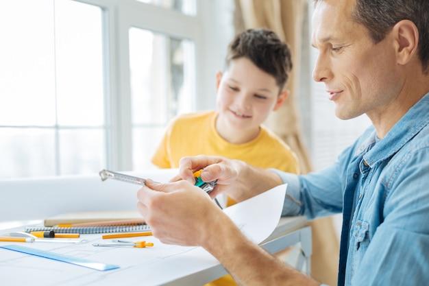 Nauwkeurige tekening. aangename pre-tienerjongen die aan de tafel in het kantoor van zijn vader zit en hem ziet werken aan de blauwdruk, het meetlint controleert