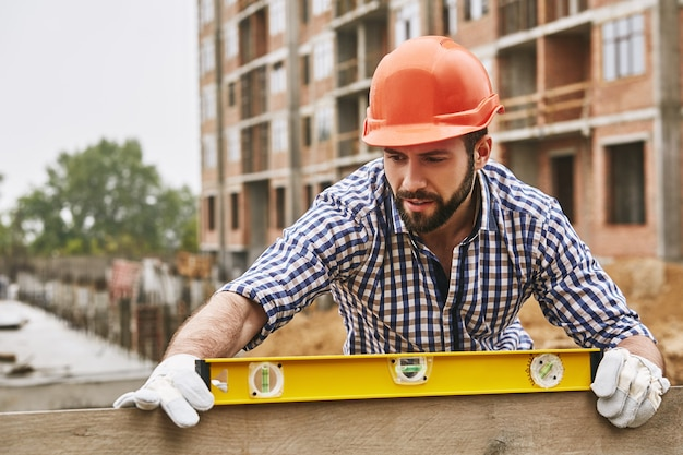 Nauwkeurigheid en kwaliteit bouwvakker in beschermende gele helm die het niveau van een plank controleert