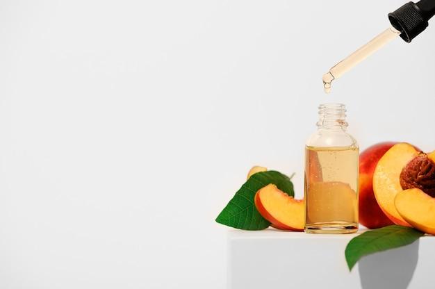 Nectarine etherische olie op een witte achtergrond. aromatherapie fruit spa olie voor huidverzorging. alternatieve homeopathische geneeskunde in een transparante fles met een pipet. ruimte kopiëren.