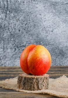 Nectarine met stuk zak, hout hout zijaanzicht op houten en grungy muur