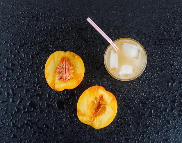 Nectarine plakjes met ijzig sap plat op een donkergrijze ondergrond