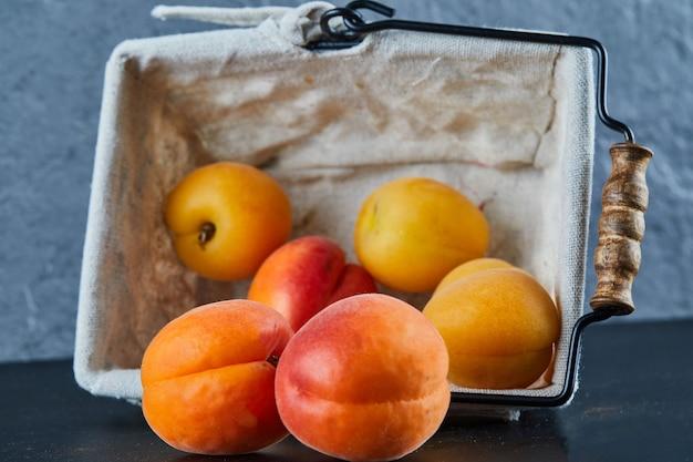 Nectarines en abrikozen in mand op blauwe ondergrond
