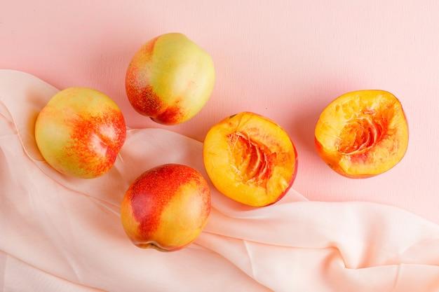 Nectarines en segmenten op roze en textiel tafel. plat lag.