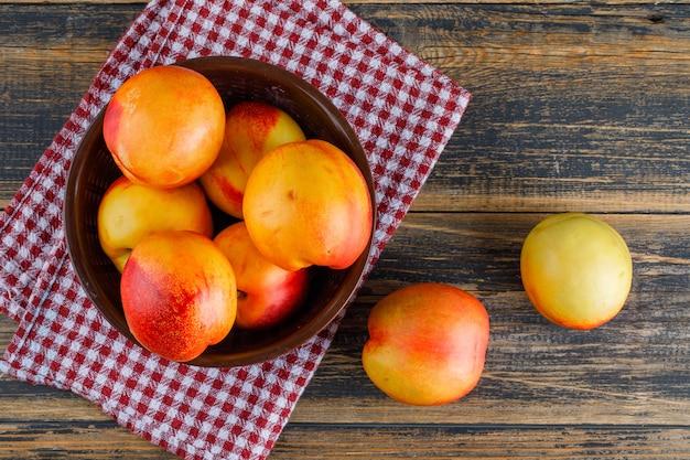 Nectarines in een kom op houten en keukenhanddoek