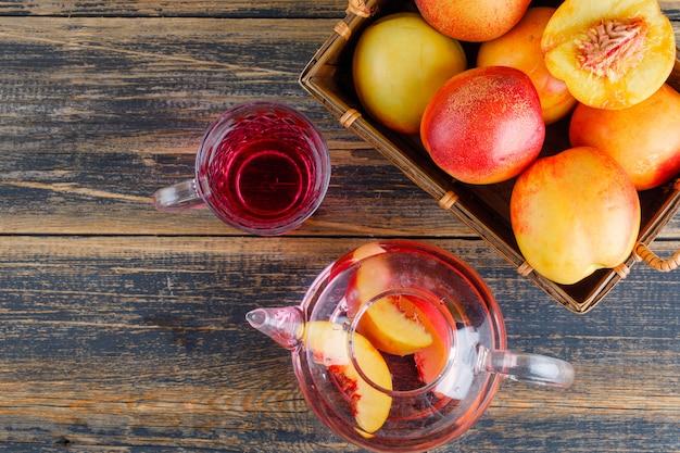 Nectarines in een mand met koud drankje bovenaanzicht op een houten tafel