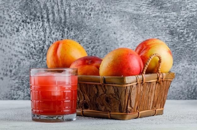 Nectarines in een mand met sap zijaanzicht op een grungy muur