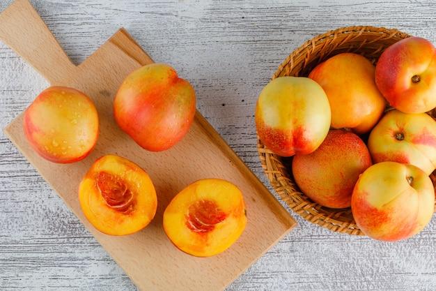 Nectarines in een mand op grungy en snijplank tafel. plat lag.