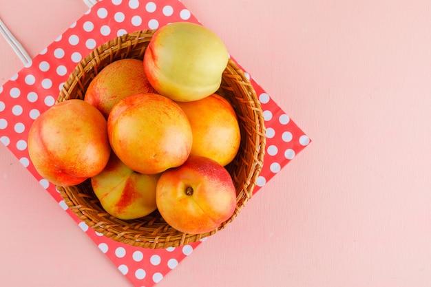Nectarines in een mand op roze en papieren zak achtergrond. plat lag.
