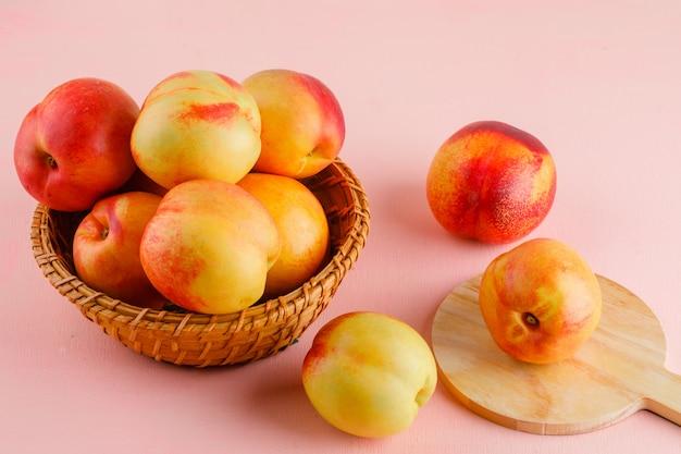 Nectarines in een mand op roze en snijplank tafel. hoge hoekmening.