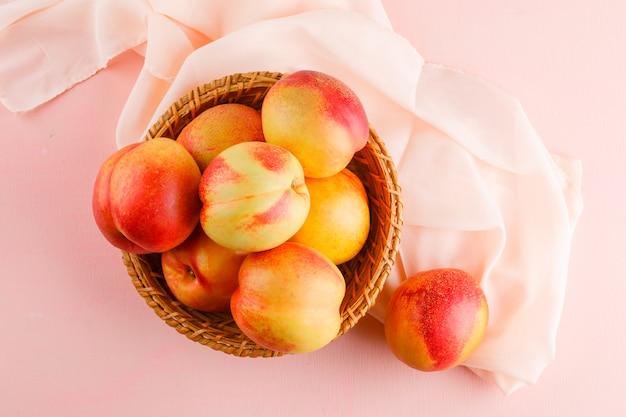Nectarines in een mand op roze en textiel oppervlak. bovenaanzicht.