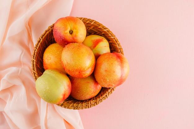 Nectarines in een mand op roze en textiel oppervlak, plat lag.
