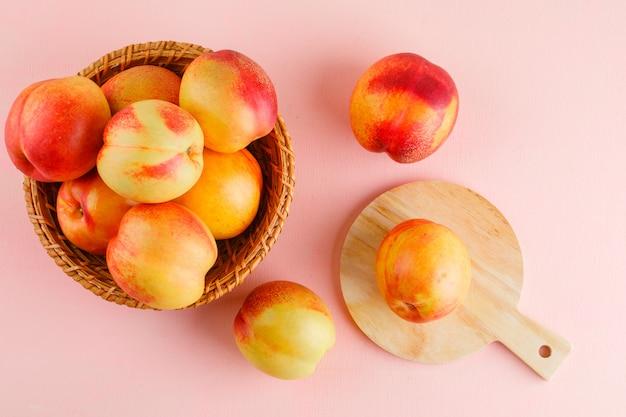Nectarines in een mand plat lag op roze en snijplank tafel