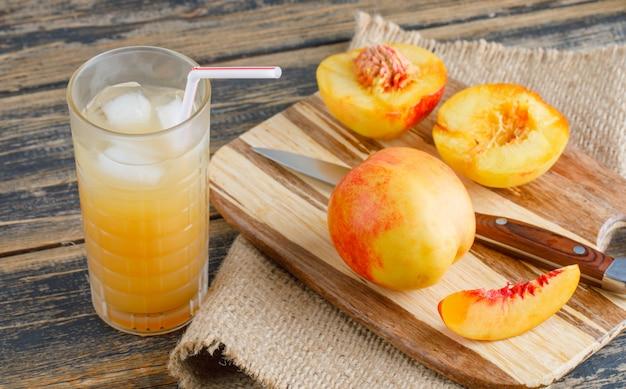 Nectarines met snijplank, sap, mes op houten en stuk zak