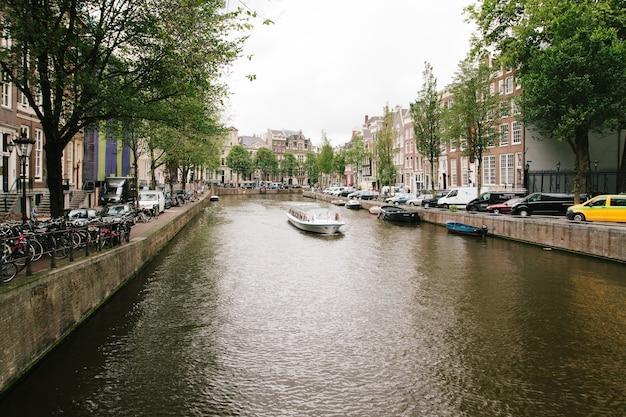 Nederland, amsterdam - juni 15,2017: veiw op de brug door het rivierkanaal met een rondvaartboot, foto van grachten in amsterdam