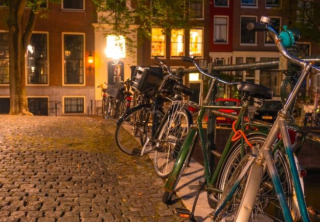 Nederland. nacht amsterdam. meerdere fietsen staan geparkeerd bij het kanaalhek op het geplaveide trottoir