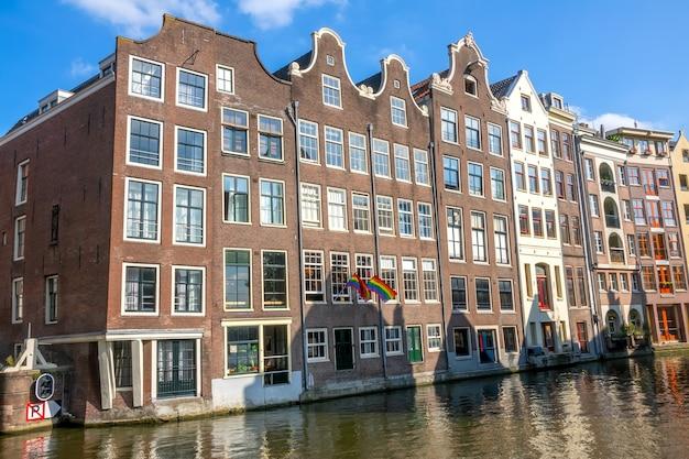 Nederland. zonnige dag op de amsterdamse gracht. traditionele huizen en twee vlaggen van de lgbt-gemeenschap op de gevel