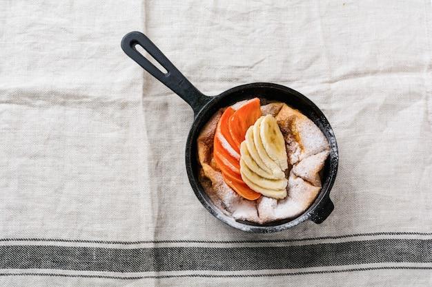 Nederlandse baby pannenkoek met appel, kaki, banaan, kaneel in kleine ijzeren pan op houten tafel oppervlak. bovenaanzicht.