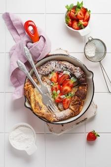 Nederlandse babypannekoek met verse aardbeibes en bestrooid met poedersuikerpoeder in rode pan op witte keukenmuur. bovenaanzicht.