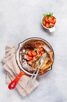 Nederlandse babypannenkoek met verse aardbeibes en bestrooid met poedersuikerpoeder in rode pan op witte keukenachtergrond. bovenaanzicht.