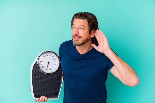 Nederlandse man van middelbare leeftijd die een schaal houdt die op blauwe achtergrond wordt geïsoleerd die probeert een roddel te luisteren.