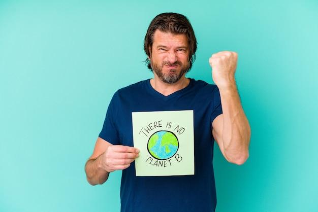 Nederlandse man van middelbare leeftijd met een er is geen bordje met planeet b op blauw met vuist, agressieve gezichtsuitdrukking.