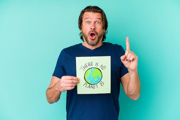 Nederlandse man van middelbare leeftijd met een er is geen plakkaat van planeet b geïsoleerd op een blauwe achtergrond met een geweldig idee, concept van creativiteit.