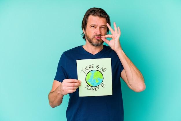 Nederlandse man van middelbare leeftijd met een er is geen plakkaat van planeet b geïsoleerd op een blauwe achtergrond met vingers op de lippen die een geheim houden.