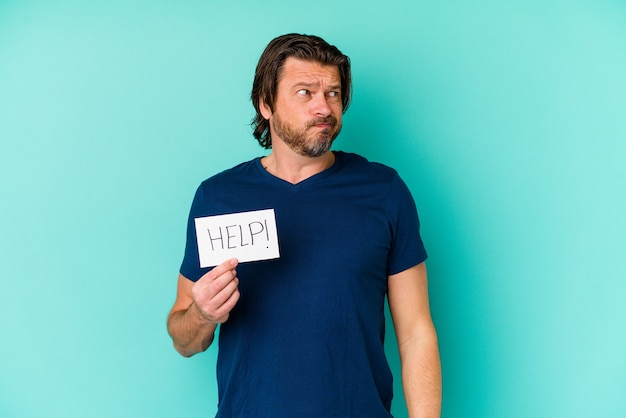 Nederlandse man van middelbare leeftijd met een hulpbordje op blauw in de war, voelt zich twijfelachtig en onzeker.