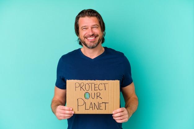 Nederlandse man van middelbare leeftijd met een plakkaat van onze planeet beschermen geïsoleerd op blauwe muur blij, lachend en vrolijk