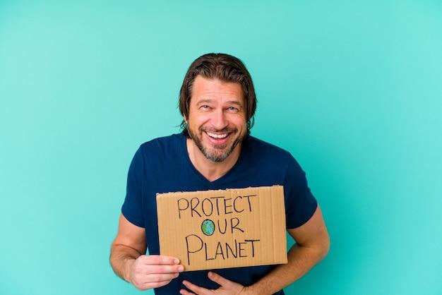 Nederlandse man van middelbare leeftijd met een plakkaat voor onze planeet, geïsoleerd op een blauwe achtergrond, lachen en plezier maken.