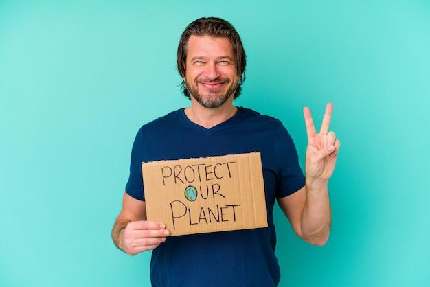 Nederlandse man van middelbare leeftijd met een plakkaat voor onze planeet, geïsoleerd op een blauwe achtergrond met nummer twee met vingers.