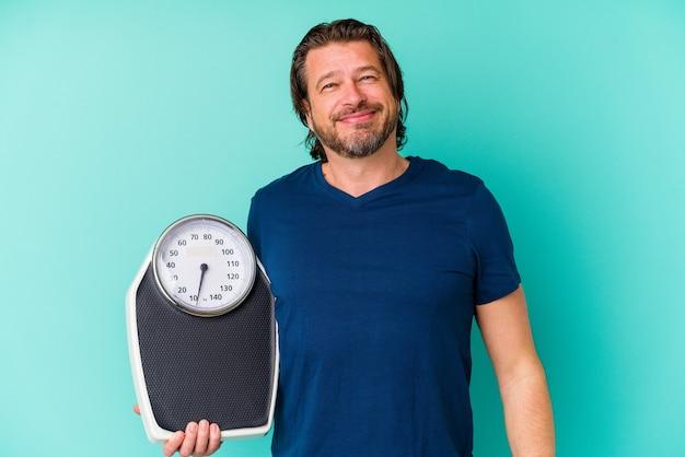 Nederlandse man van middelbare leeftijd met een schaal geïsoleerd op blauwe muur blij, lachend en vrolijk