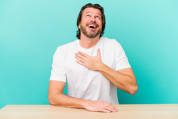 Nederlandse man van middelbare leeftijd zit geïsoleerd op blauwe achtergrond lacht hardop terwijl hij de hand op de borst houdt.