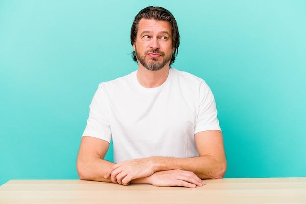 Nederlandse man van middelbare leeftijd zittend op blauw in de war, voelt zich twijfelachtig en onzeker.