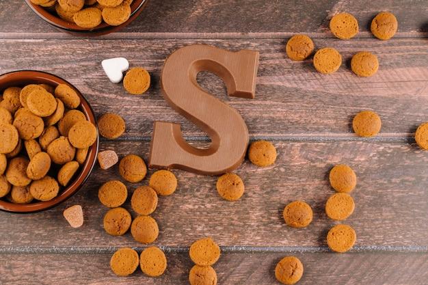 Nederlandse vakantie sinterklaas. achtergrond met traditionele gerechten - pepernoten, chocolade letter, strooigoed snoep en wortelen voor paard.