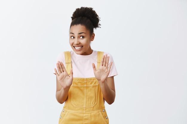 Nee, alles is in orde. intens bezorgd en nerveus schattig afrikaans vrouwtje in gele overall, achteruit stoppend, handpalmen omhoog in de buurt van de borst in droevig gebaar, per ongeluk tegen vreemdeling stoten
