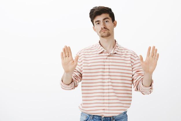 Nee, dank u wel. portret van onverschillige onbezorgde aantrekkelijke man met somber gezicht, palmen in stop of genoeg gebaar trekken, verkoper stoppen en aanbod afwijzen, staande