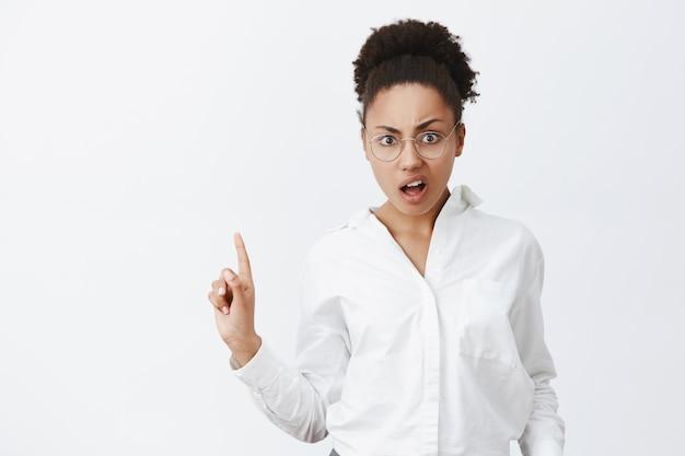 Nee, echt niet. portret van vrouwelijke ontevreden en pissige aantrekkelijke emotionele donkere vrouw met krullend haar, gebaren met vinger in geen of weigerend gebaar, staande over grijze muur