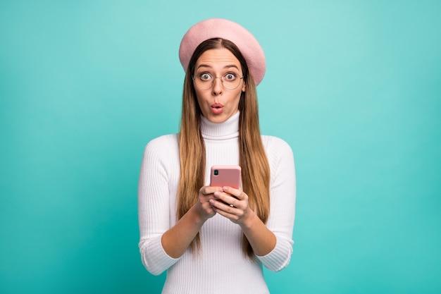 Nee! foto van aantrekkelijke geschokte dame houd telefoon lees nieuwe post negatieve opmerkingen draag specificaties moderne roze baret pet witte coltrui geïsoleerde heldere groenblauw kleur achtergrond