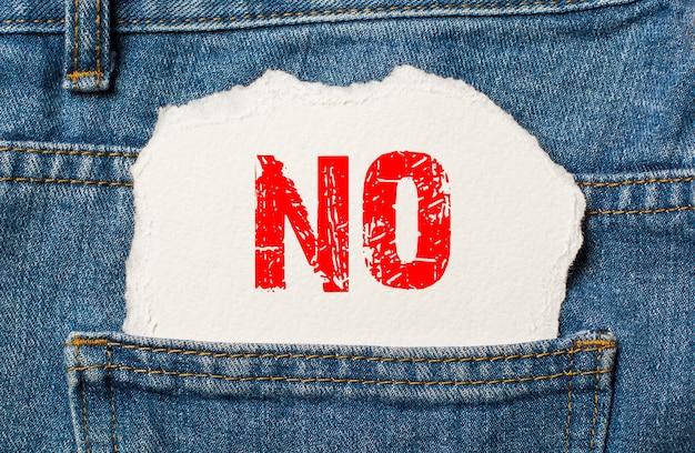 Nee op wit papier in de zak van blauwe spijkerbroek