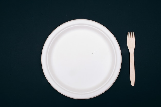 Nee tegen plastic. houten, milieuvriendelijke papieren bord en vork op donkere achtergrond, bovenaanzicht. tijd om te veranderen. nieuwe regels om plastic afval te verminderen, eu-richtlijn. verbied plastic voor eenmalig gebruik.