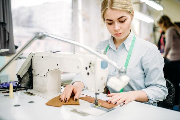 Needlewoman naait stoffen op een naaimachine. kleermakerij of kleermakerij op kledingfabriek, handwerk, naaister in werkplaats
