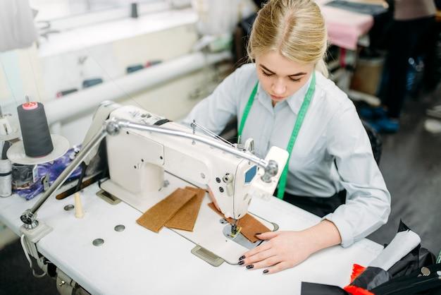 Needlewoman naait stoffen op een naaimachine