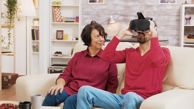 Neef laat zijn grootmoeder zien hoe hij een vr-bril in de woonkamer moet gebruiken.