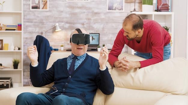 Neef laat zijn grootvader zien hoe hij een vr-headset in de woonkamer moet gebruiken.
