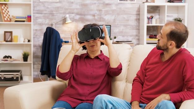 Neef leert zijn grootmoeder hoe hij een virtual reality-headset moet gebruiken in de woonkamer